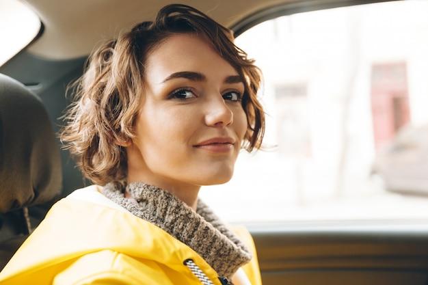 La giovane signora graziosa si è vestita in impermeabile che si siede in automobile.