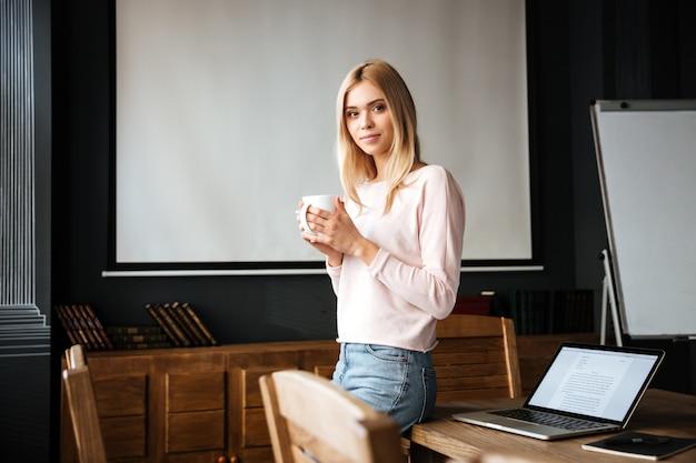 La giovane signora sorridente che sta nel caffè lavora con il computer portatile