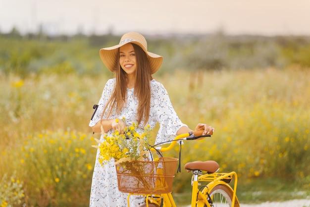 La giovane signora sorridente sta camminando con la sua bicicletta su un campo di fiori gialli