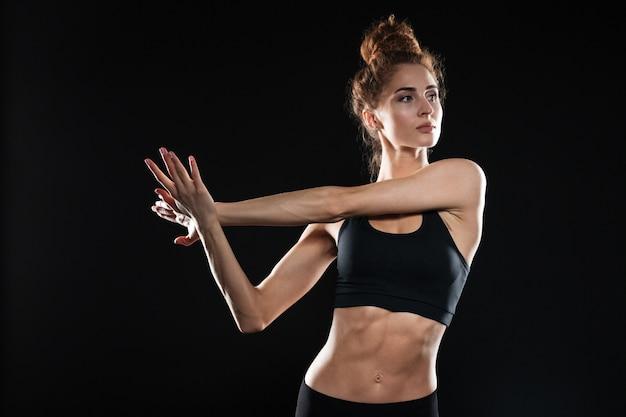 La giovane signora sportiva concentrata fa esercizi di stretching.