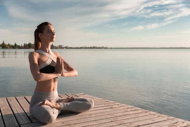 La giovane signora sportiva in spiaggia fa esercizi di meditazione.