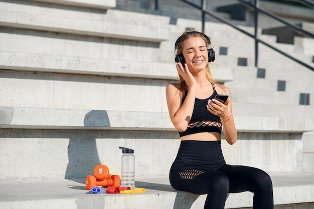 La giovane sportiva in buona salute attraente ascolta musica con le cuffie durante l'allenamento allo stadio.