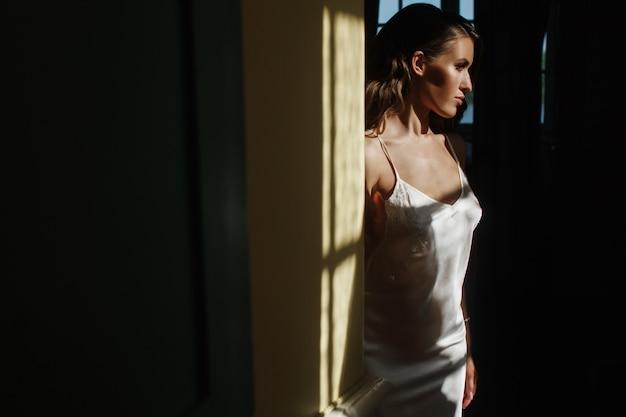 La giovane sposa seducente in un vestito di seta si siede sul davanzale della finestra nel primo mattino