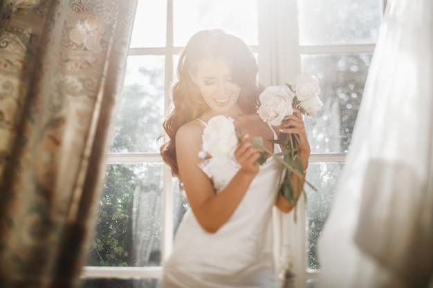 La giovane sposa tiene un bouuqet di peonie che si trovano sul davanzale della finestra nella luminosa mattina