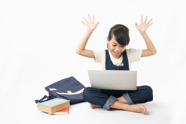 La giovane studentessa allegra e felice asiatica che guarda sul computer portatile isolato su fondo bianco, cerca internet e ottiene la conoscenza
