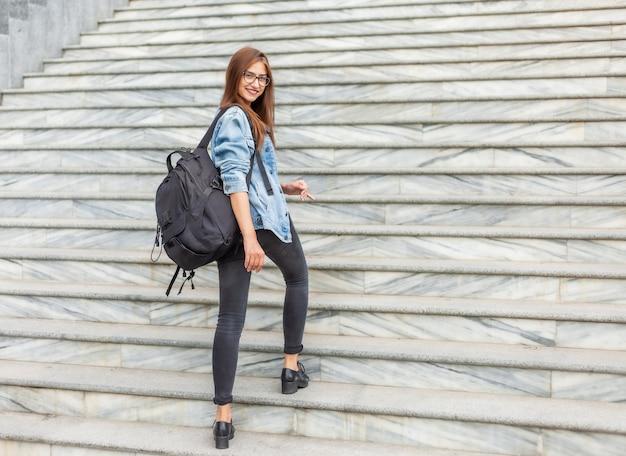 La giovane studentessa allegra in una giacca di jeans e gli occhiali con un grande zaino sale le scale della città. concetto di gioventù