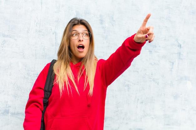 La giovane studentessa carina si sente scioccata e sorpresa indicando e guardando verso l'alto in soggezione con stupito sguardo a bocca aperta