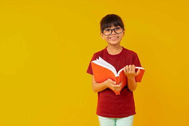 La giovane studentessa dell'asia con i grandi vetri da portare sorrisi e la camicia rossa aprono e leggono il libro