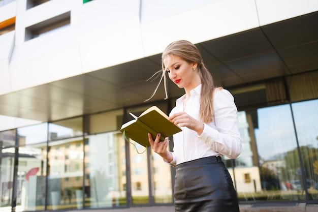 La giovane studentessa guarda nel suo diario. elegante studentessa con un libro in mano si sta preparando per le lezioni