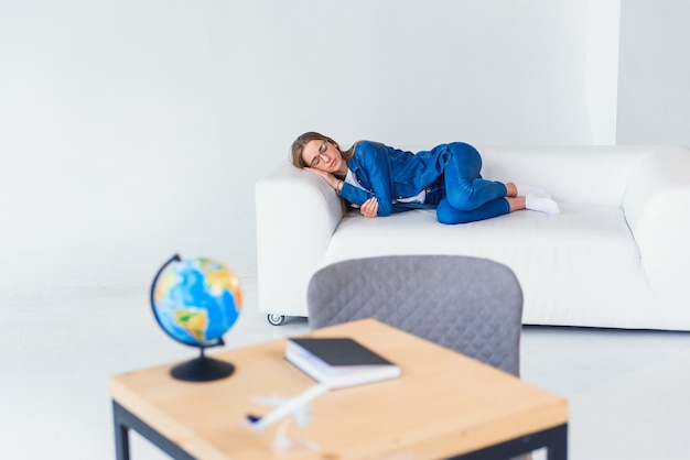 La giovane studentessa stanca in abbigliamento casual dorme sul sofà bianco. bella donna che riposa dopo una dura giornata di studio o di lavoro.