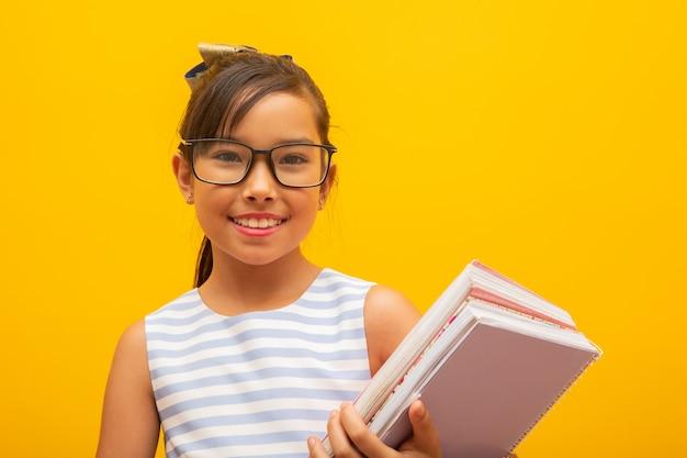 La giovane tenuta asiatica della ragazza dello studente prenota su fondo giallo