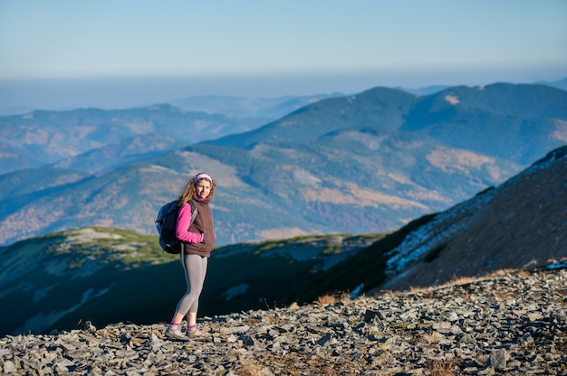 La giovane viandante felice della donna sta camminando sulla montagna platone