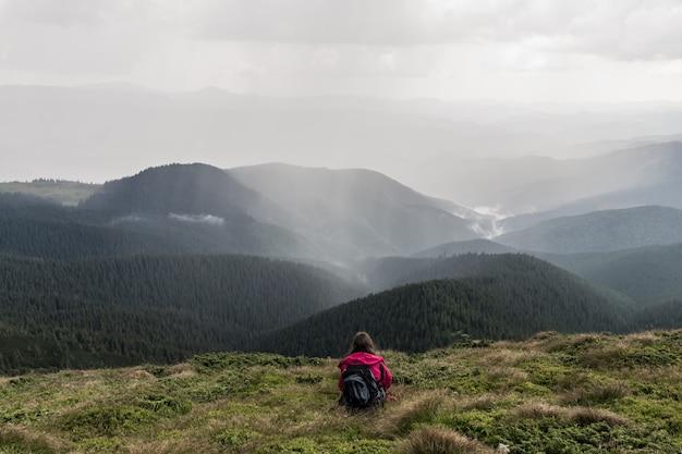 La giovane viandante femminile con lo zaino si siede in erba sopra la collina