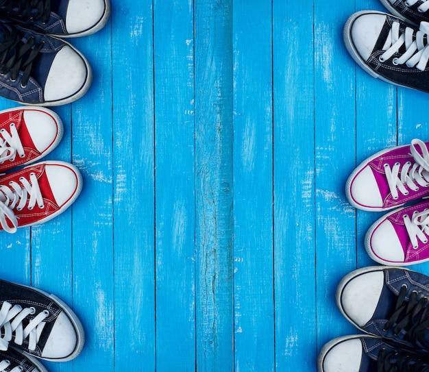 La gioventù ha colorato le scarpe da tennis su un fondo blu delle plance di legno