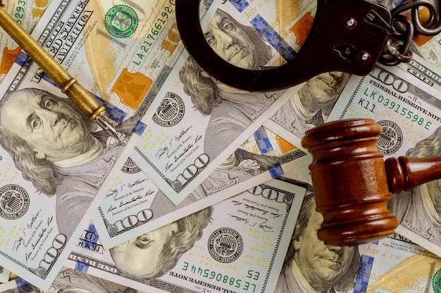 La giustizia e il concetto di legge incassano i dollari in banconote giudicano il martelletto con le manette
