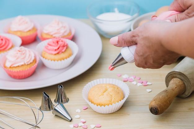 La glassa di vaniglia cremosa viene roteata su torte di tazza di dimensioni individuali