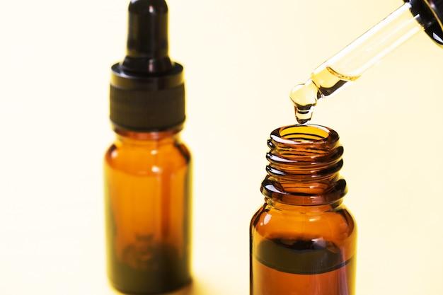 La goccia cade dalla pipetta. bottiglia di olio cosmetico con una pipetta. copia spazio. messa a fuoco selettiva.