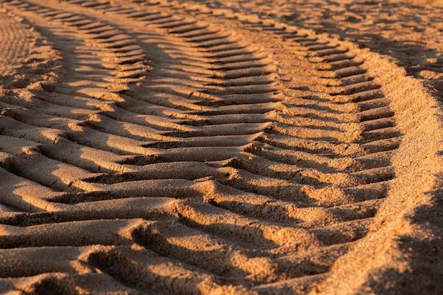 La gomma di automobile stampa sulla sabbia durante il giorno, fuoco selettivo.