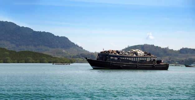La grande barca trasporta merci attraverso l'isola