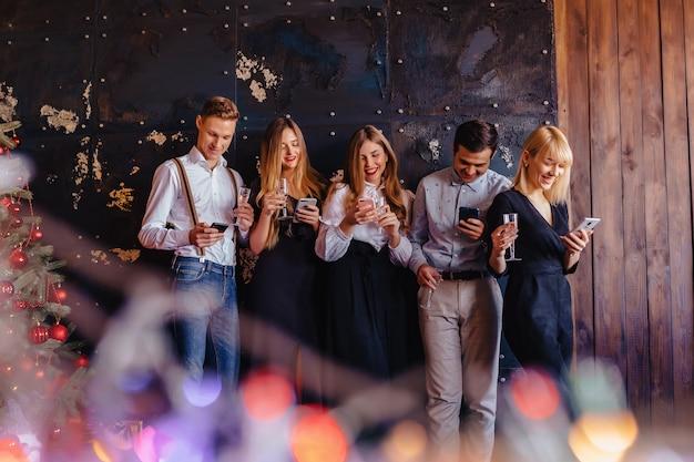 La grande compagnia festeggia un nuovo anno con bicchieri di champagne con i telefoni mania