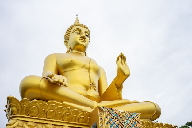 La grande statua dorata del buddha si erge alta