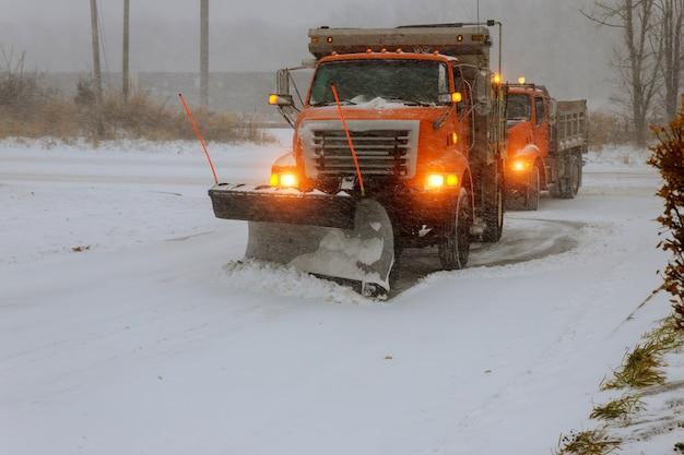La grande strada della neve di rimozione del trattore durante la bufera di neve della neve