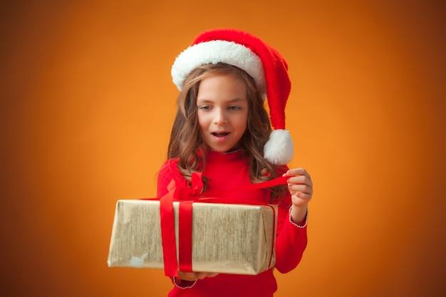 La graziosa bambina allegra con cappello da babbo natale e regalo su sfondo arancione