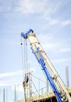 La gru di costruzione per il sollevamento pesante contro un cielo blu indietro