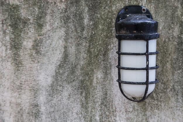 La lampada d'epoca su sfondo grigio muro di cemento