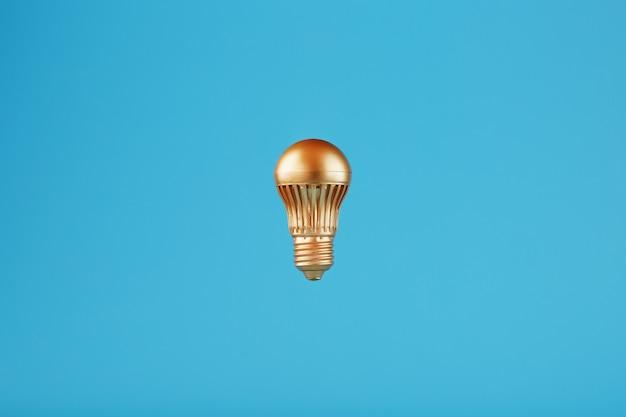 La lampadina è d'oro su una parete blu.