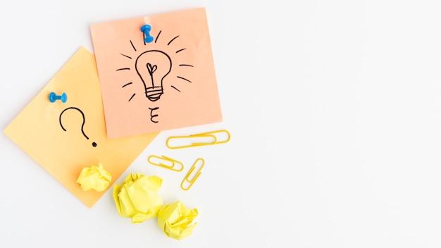 La lampadina e il punto interrogativo tirati firmano sulla nota adesiva allegata con la puntina da disegno sopra fondo bianco