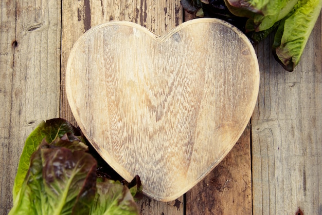 La lattuga lascia sul tagliere a forma di cuore, su di legno. preparazione di insalata e cibi sani. cavolo lattuga copyspace.
