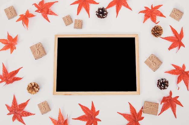 La lavagna della superficie di legno della composizione in autunno ha decorato le foglie di acero variopinte su bianco
