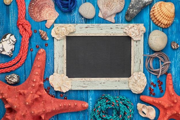 La lavagna in bianco con le conchiglie, le pietre, la corda e la stella pescano sulla tavola di legno blu, copiano lo spazio