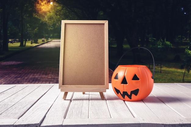 La lavagna sul basamento con le zucche di halloween sul pavimento di legno e sul fondo nero