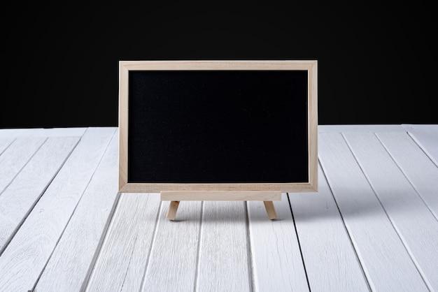 La lavagna sul pavimento di legno e sfondo nero