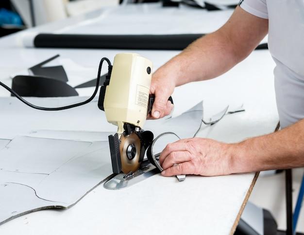 La lavoratrice usa la macchina elettrica del tessuto di taglio. linea di produzione dell'industria tessile.