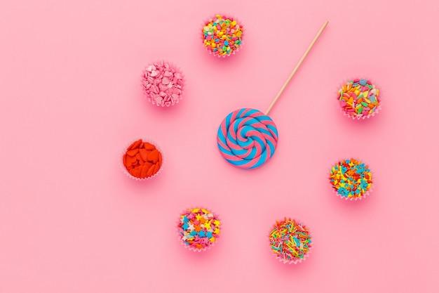 La lecca-lecca e lo zucchero spruzza in ciotole di carta su fondo rosa, vista superiore