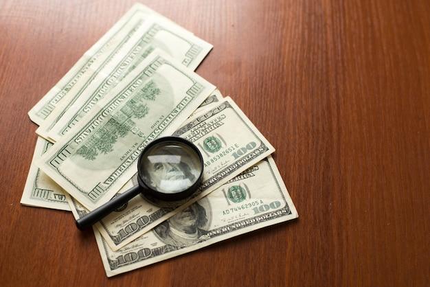 La lente d'ingrandimento si trova sui dollari americani su fondo di legno