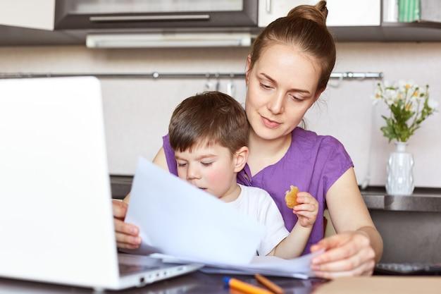 La libera professionista madre in congedo di maternità lavora con documentazione