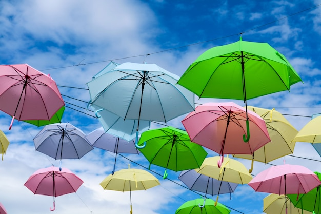 La linea di ombrello operata variopinta decora muoversi all'aperto dal vento sulla nuvola di bianco del cielo blu