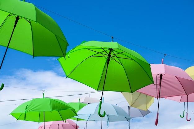 La linea di ombrello variopinta decora muoversi all'aperto dal vento sulla nuvola di bianco del cielo blu