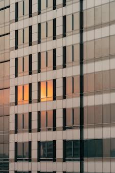 La luce arancione del tramonto si riflette sulla facciata del vetro e del rivestimento di sera.
