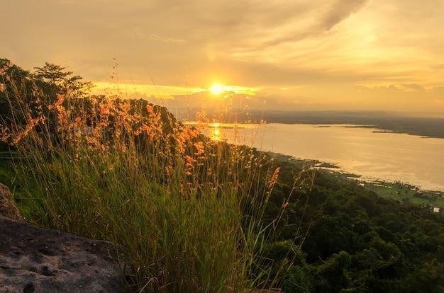 La luce del sole riflette la superficie dell'acqua e l'erba è sulle montagne