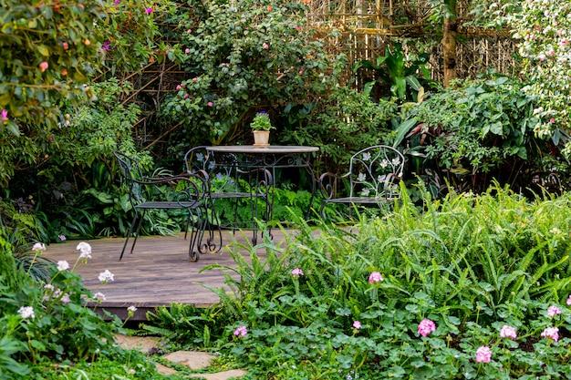 La luce e l'ombra dei tavoli e delle sedie nel giardino fiorito