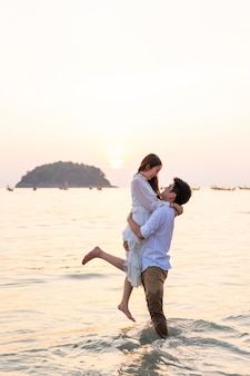 La luna di miele andante delle coppie felici viaggia sulla spiaggia di sabbia tropicale di estate