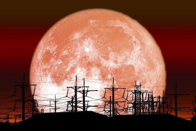 La luna piena rossa del latte appoggia sul palo elettrico della siluetta su cielo notturno