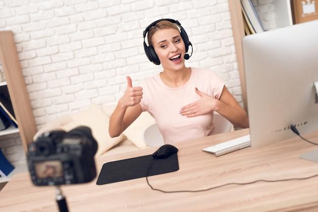 La macchina fotografica spara al podcaster della donna che posa per il podcast radiofonico.