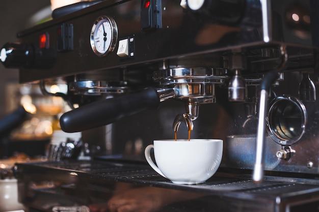 La macchina per il caffè versa appena un caffè in una tazza bianca