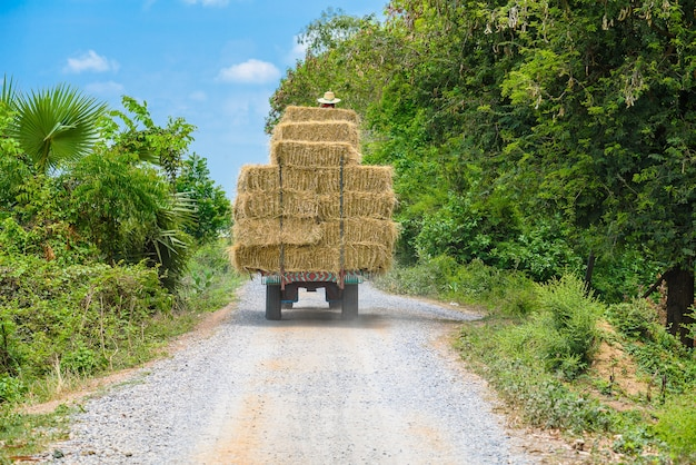 La macchina trasportava balle di paglia su una strada di campagna